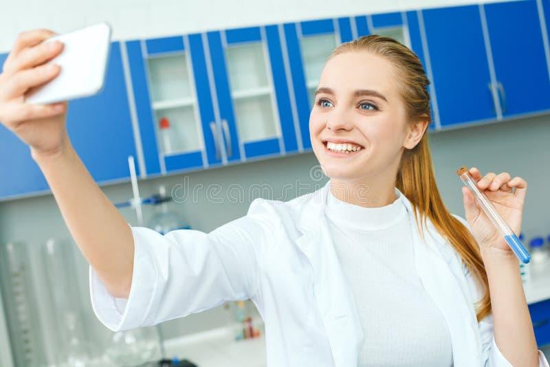 Jonge chemieleraar in het werk bevindende selfie foto's van het schoollaboratorium royalty-vrije stock afbeelding