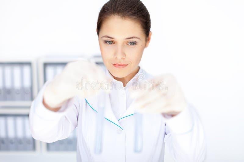 Jonge chemische vrouwelijke onderzoeker die twee glasbuizen met FL houden royalty-vrije stock fotografie