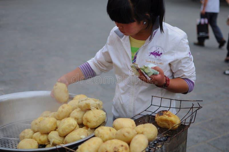 Jonge Chinese meisjes verkopende aardappels in de straat stock afbeeldingen