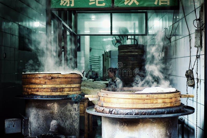 Jonge Chinese vrouw die bollen voorbereiden bij een klein restaurant van het straatrestaurant stock foto