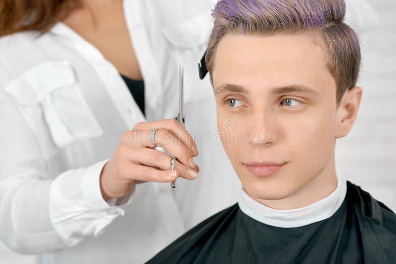 Jonge cliënt die met gestemd lilac haar het witte hairstyling zitten royalty-vrije stock afbeeldingen