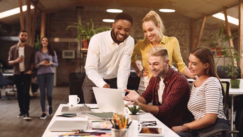 Jonge collega's die ideeën in het coworking van bureau bespreken stock foto's
