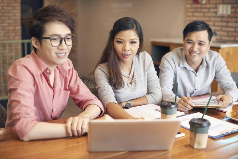 Jonge collega's met laptop op koffiepauze stock foto