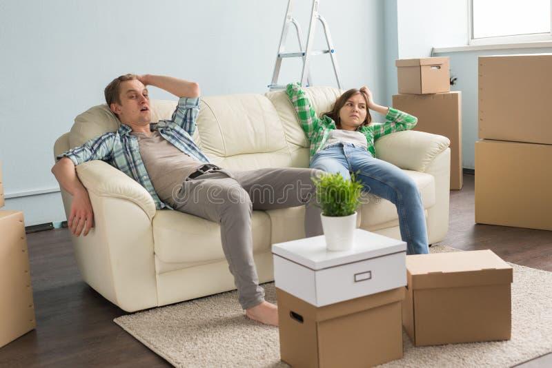 Jonge cople die rust hebben terwijl zich het bewegen in een nieuwe flat stock afbeelding