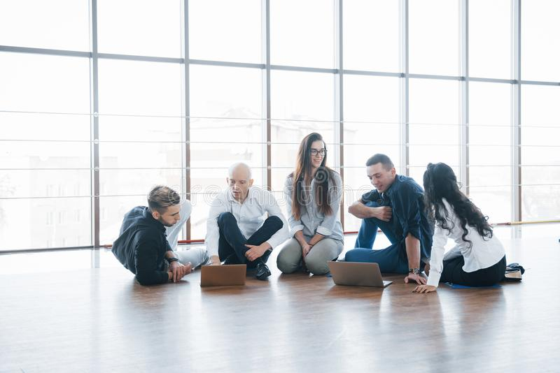 Jonge creatieve mensen in modern bureau De groep jonge bedrijfsmensen werkt samen met laptop freelancers stock foto