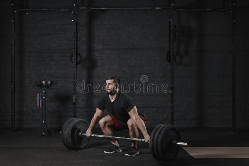 Jonge crossfitatleet die deadlift oefening met zware barbell doen bij gymnastiek Mens die functionele opleidings powerlifting tra royalty-vrije stock afbeelding