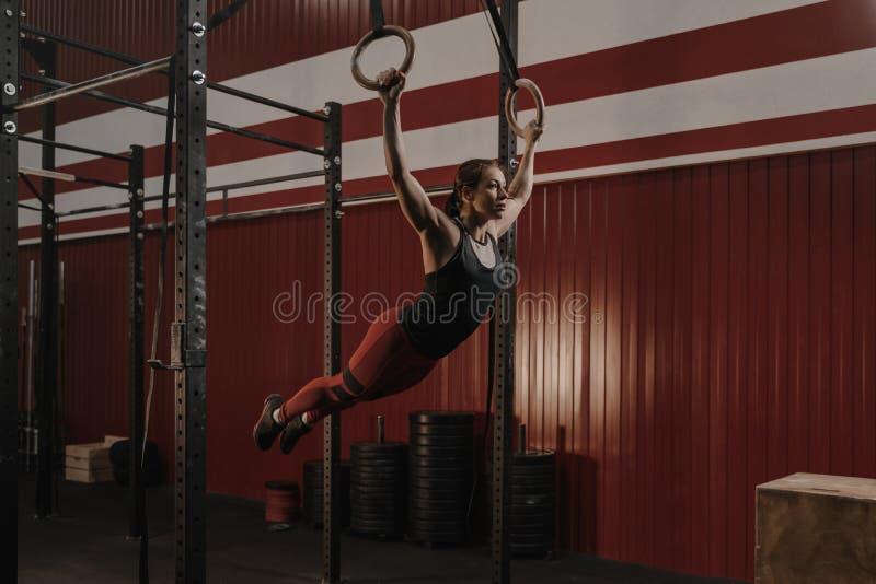 Jonge crossfitvrouw die op gymnastiek- ringen slingeren stock afbeelding