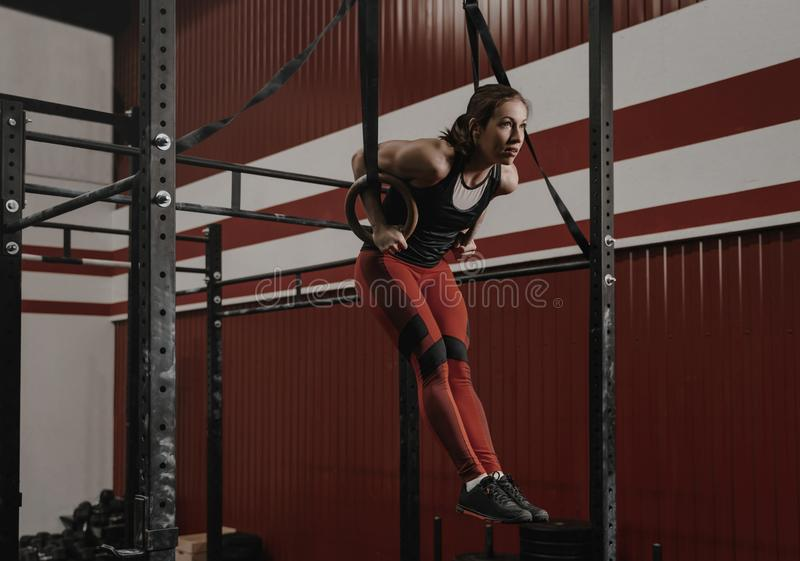 Jonge crossfitvrouw die spier-UPS op gymnastiek- ringen doen bij de gymnastiek stock afbeelding