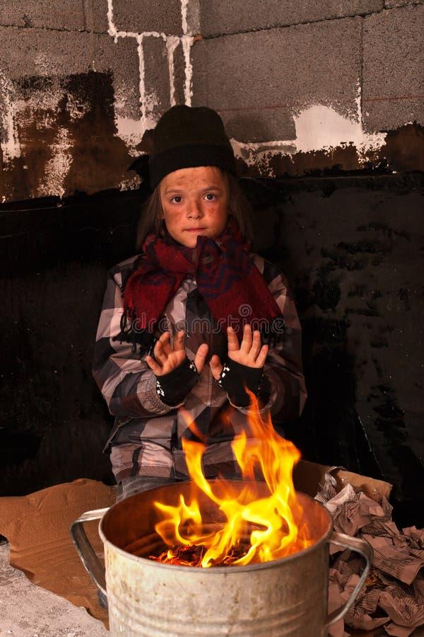 Jonge dakloze jongen op de straat die zijn handen verwarmen stock fotografie
