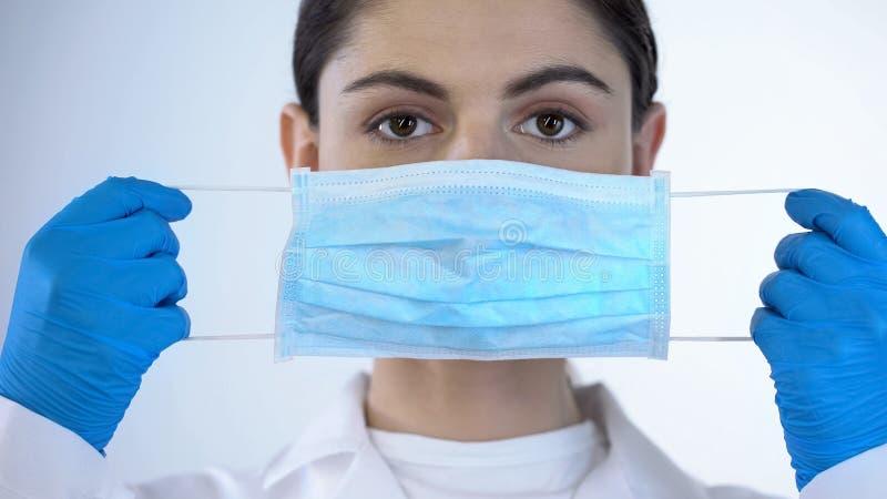 Jonge dame arts die op chirurgisch masker, veiligheid zetten terwijl het onderzoeken, close-up royalty-vrije stock afbeeldingen