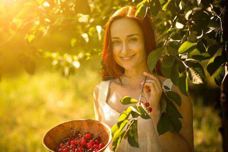 Jonge dame in de tuin het plukken kersen in een kom stock afbeeldingen