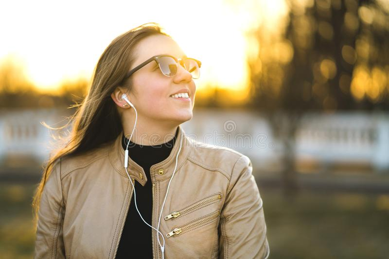 Jonge dame die aan muziek met kleine witte hoofdtelefoons luisteren stock fotografie