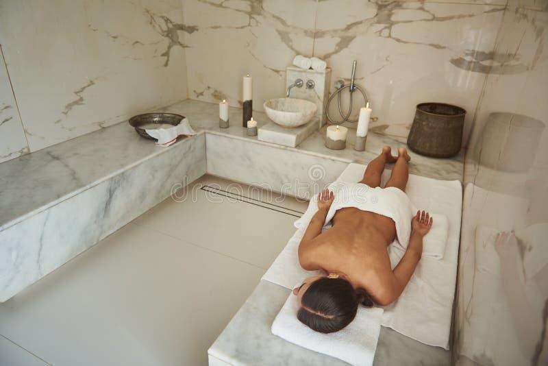 Jonge dame die alleen in de marmeren ruimte van Turks bad liggen royalty-vrije stock afbeeldingen