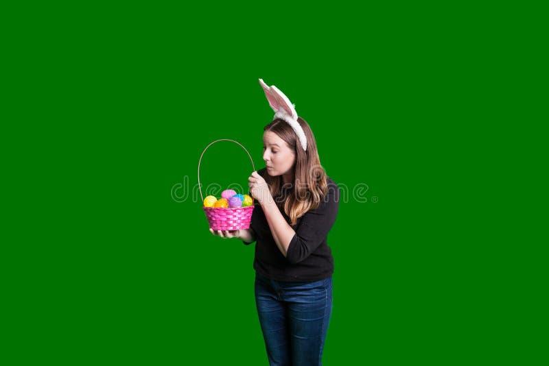 Jonge dame die en binnen een mand steunen kijken die van het vakantiepaasei konijntjesoren dragen stock afbeelding