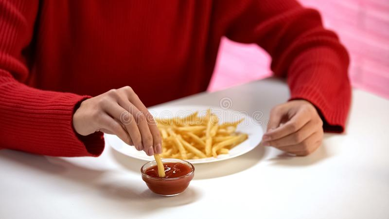 Jonge dame die Frans-gebraden aardappel in tomatensaus, schadelijke maaltijd, calorie?n onderdompelen royalty-vrije stock foto