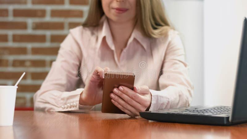 Jonge dame die Internet doorbladeren, die nieuws op smartphonekoffie lezen, sociale netwerken royalty-vrije stock fotografie