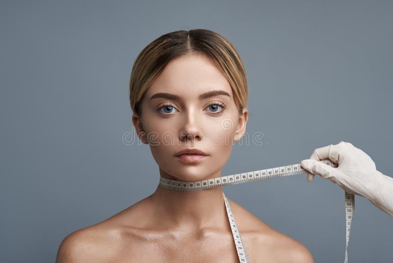 Jonge dame die kalm terwijl het hebben van het meten van band op de hals kijken stock foto
