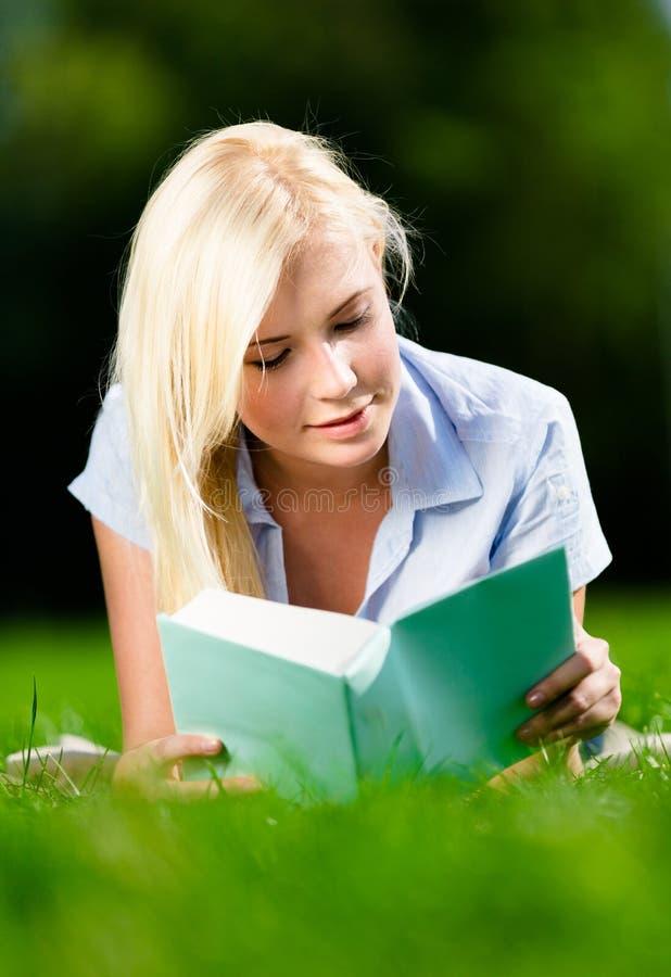 Jonge dame die op gras liggen en boek lezen stock afbeeldingen