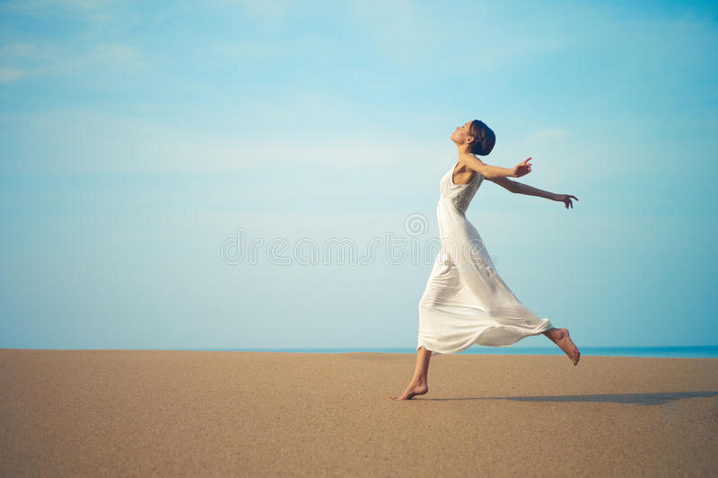 Jonge dame die op het strand springen stock foto