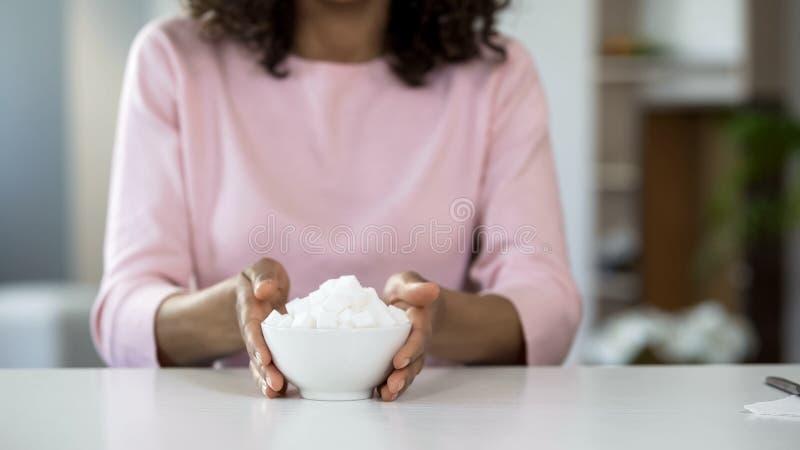 Jonge dame het standhouden kom suiker, diabetesvoorlichting, slechte voeding royalty-vrije stock foto's