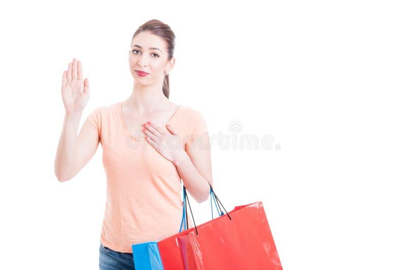 Jonge dame met het winkelen het zweren tonen of zakken die gest beloven stock afbeelding