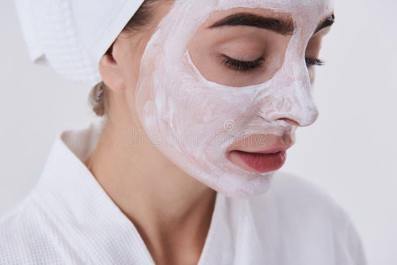 Jonge dame met kosmetisch masker op haar die gezicht op witte achtergrond wordt geïsoleerd stock afbeeldingen