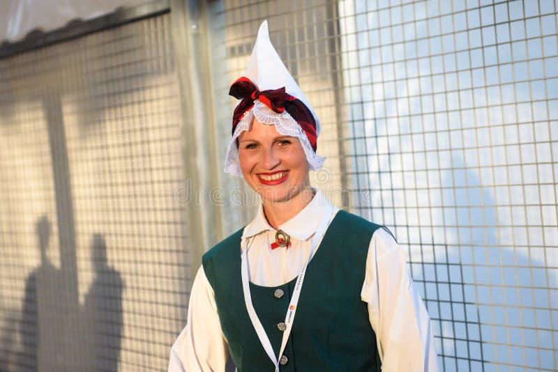 Jonge dame met traditionele Letse volkskleding vóór overleg stock fotografie