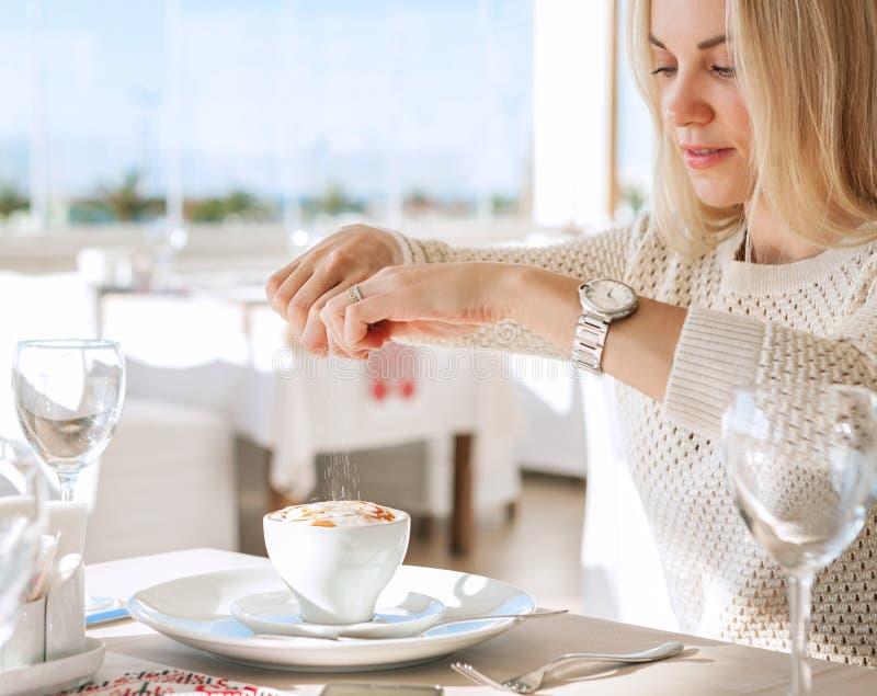 Jonge dame toegevoegde suiker in koffie stock foto's