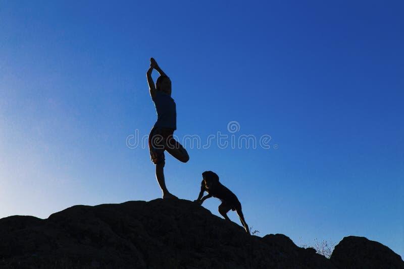 Jonge dame in yogapositie met hond op de rotsen stock foto