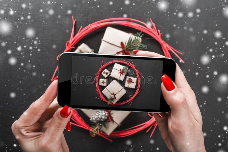 Jonge dames die een Kerstmisachtergrond met hun telefoon schieten Met de hand gemaakte giften in een rode cirkel Effect van sneeu stock fotografie
