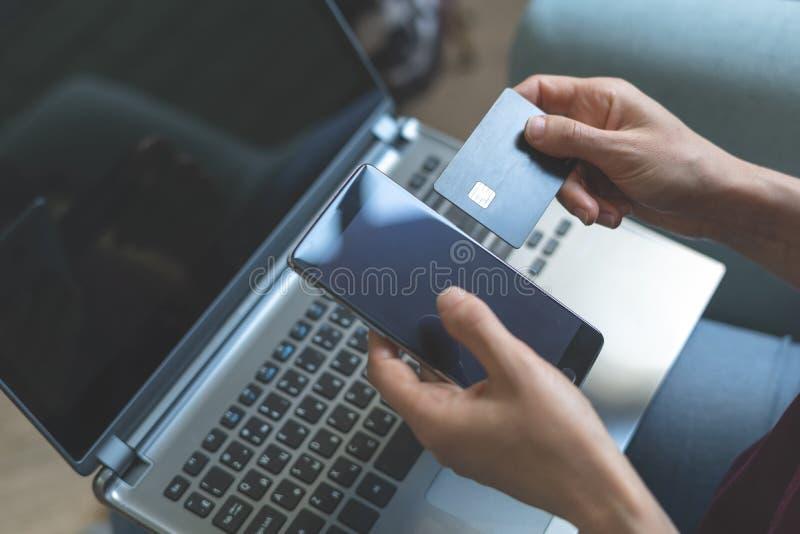 Jonge damezitting in koffie en het gebruiken van smartphone, laptop en plastic betaalpas royalty-vrije stock foto's