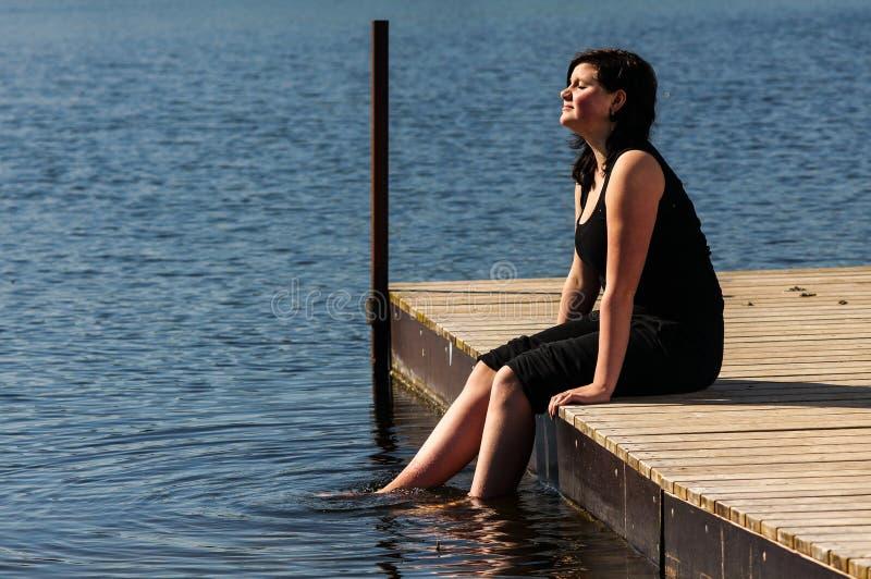 Jonge damezitting op de pier royalty-vrije stock foto