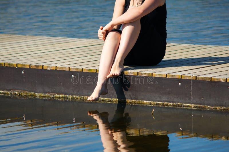 Jonge damezitting op de pier royalty-vrije stock afbeeldingen