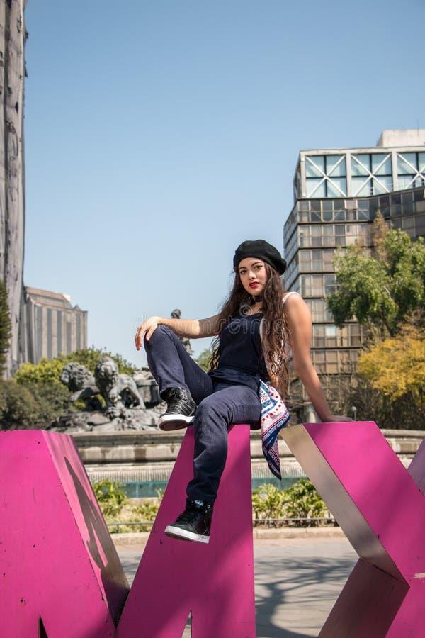 Jonge damezitting op het CDMX-beeldhouwwerk in La Condesa royalty-vrije stock afbeelding