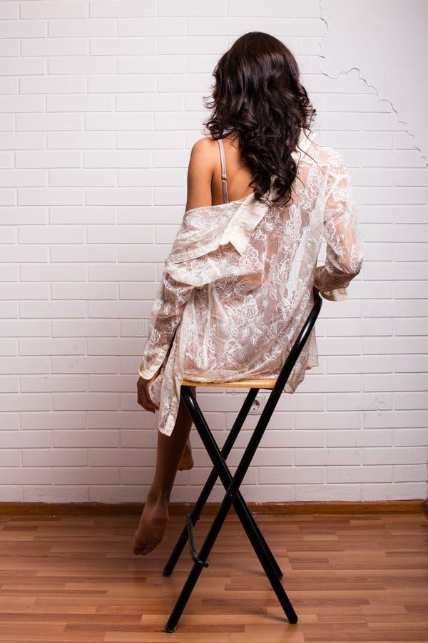 Jonge damezitting terug op een stoel stock foto's