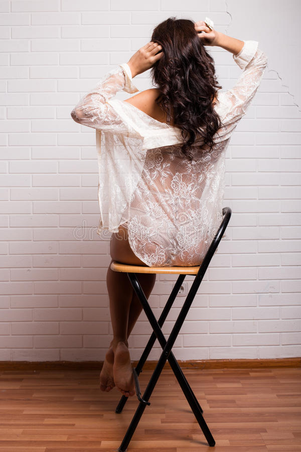 Jonge damezitting terug op een stoel stock afbeelding