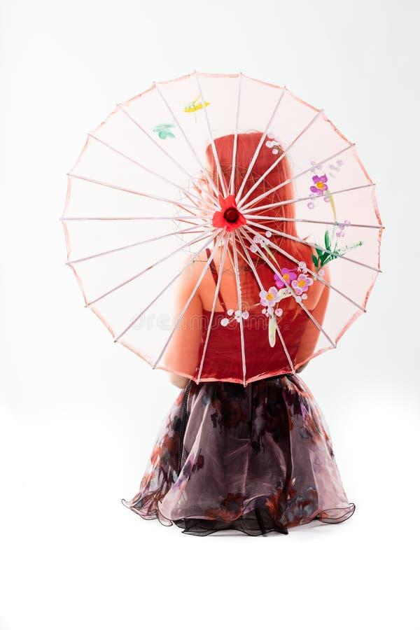 Jonge danser achter een rode Chinese paraplu royalty-vrije stock fotografie