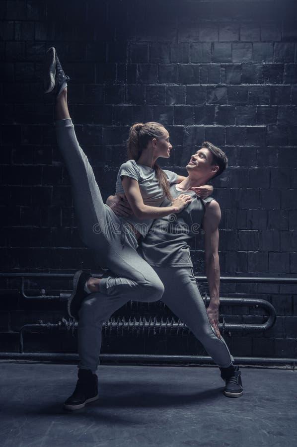 Jonge dansers die in de donkere aangestoken ruimte presteren stock fotografie