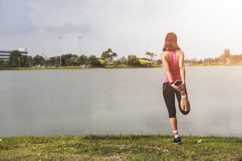 Jonge de agent van de geschiktheidsvrouw het uitrekken zich benen vóór looppas op park stock foto