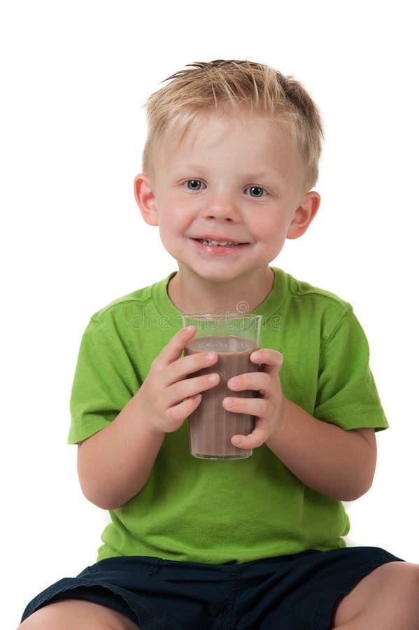 Jonge de chocolademelk van de jongensholding op wit stock fotografie