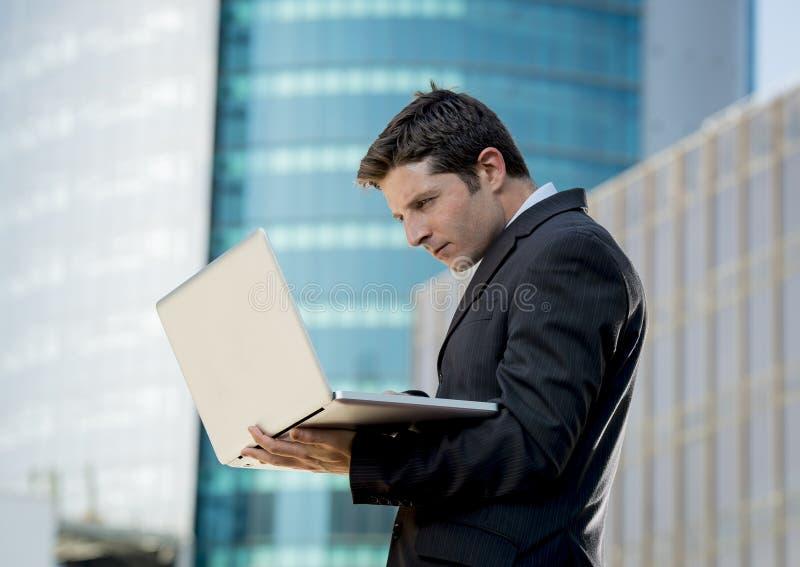 Jonge de computerlaptop die van de zakenmanholding stedelijke zaken in openlucht werken stock fotografie