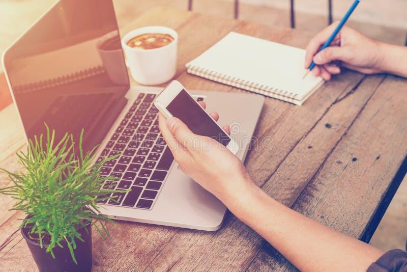 Jonge de holding van de bedrijfsmensenhand telefoon en het schrijven royalty-vrije stock fotografie