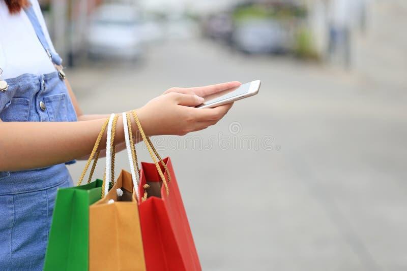 Jonge de holding van de vrouwenhand smartphone en het winkelen zakken met status bij het autoparkeerterrein royalty-vrije stock afbeelding