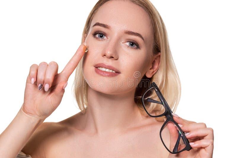 Jonge de holdingscontactlens van de blondevrouw op vinger voor haar gezicht en holding in haar andere hand zwarte glazen  stock afbeelding