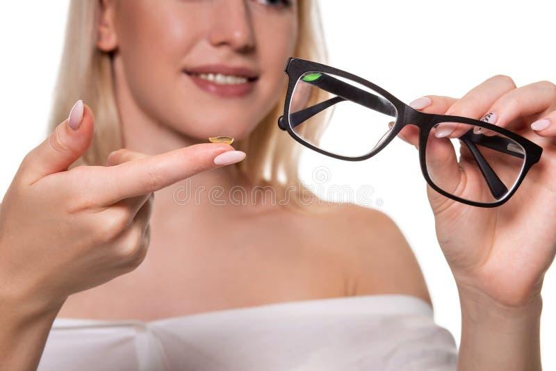 Jonge de holdingscontactlens van de blondevrouw op vinger voor haar gezicht en holding in haar andere hand zwarte glazen  royalty-vrije stock foto's