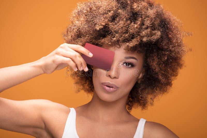 Jonge de holdingscreditcard van het afromeisje op gele achtergrond royalty-vrije stock afbeeldingen