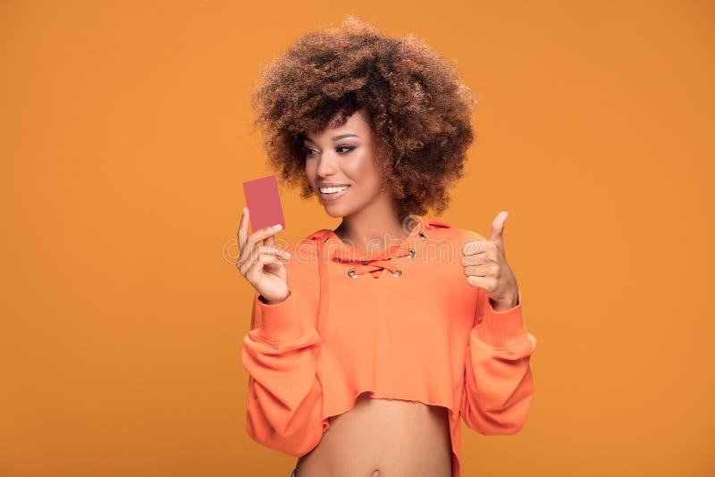Jonge de holdingscreditcard van het afromeisje op gele achtergrond stock afbeeldingen
