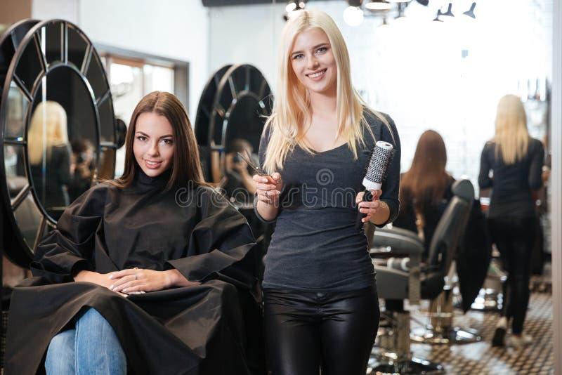 Jonge de holdingsschaar en kam van de blonde vrouwelijke kapper royalty-vrije stock foto's