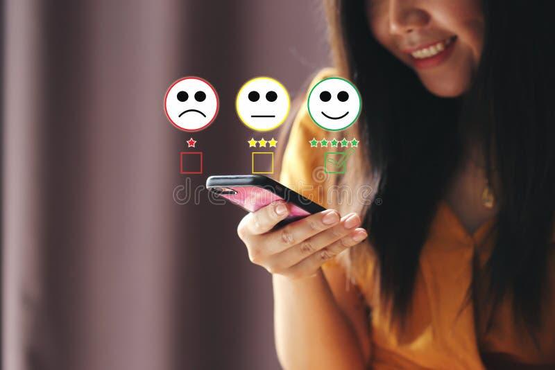 Jonge de holdingssmartphone van de vrouwenhand en het zetten van vinkje met lachebekjeteller en groene teller op vijf sterren van royalty-vrije stock fotografie
