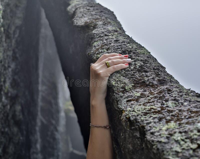 Jonge de klimmerhanden die van de vrouwenrots bij de klippenrots van de kustberg beklimmen stock fotografie